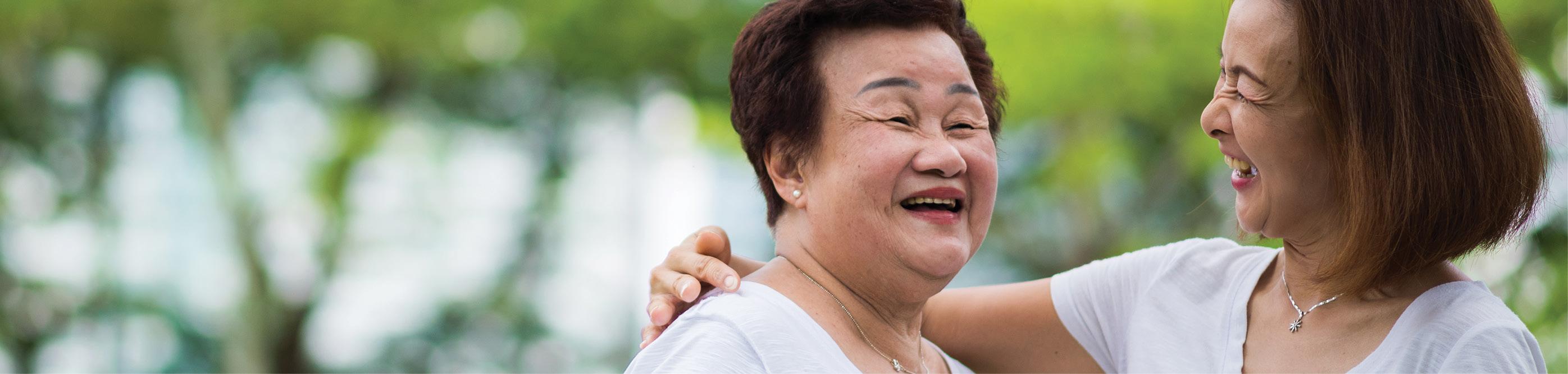 Une femme souriante enlace son bras autour de sa mère souriante