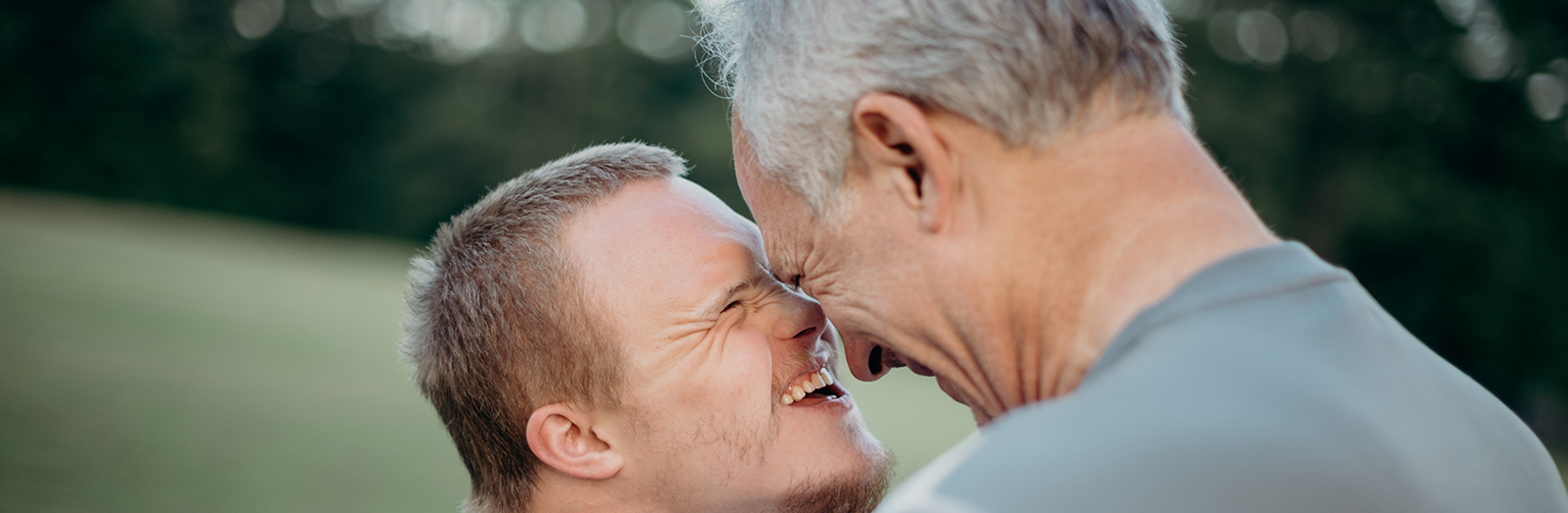 A young man with down syndrome and his father, smiling together