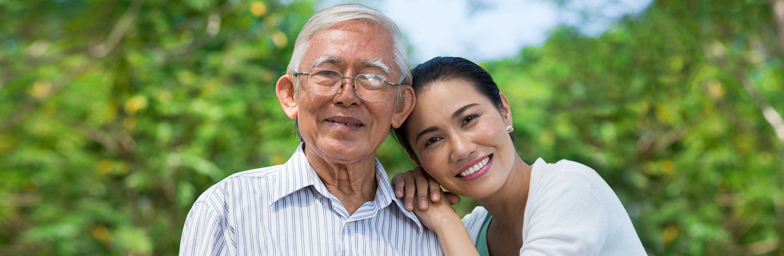 A young woman and her father, smiling outside