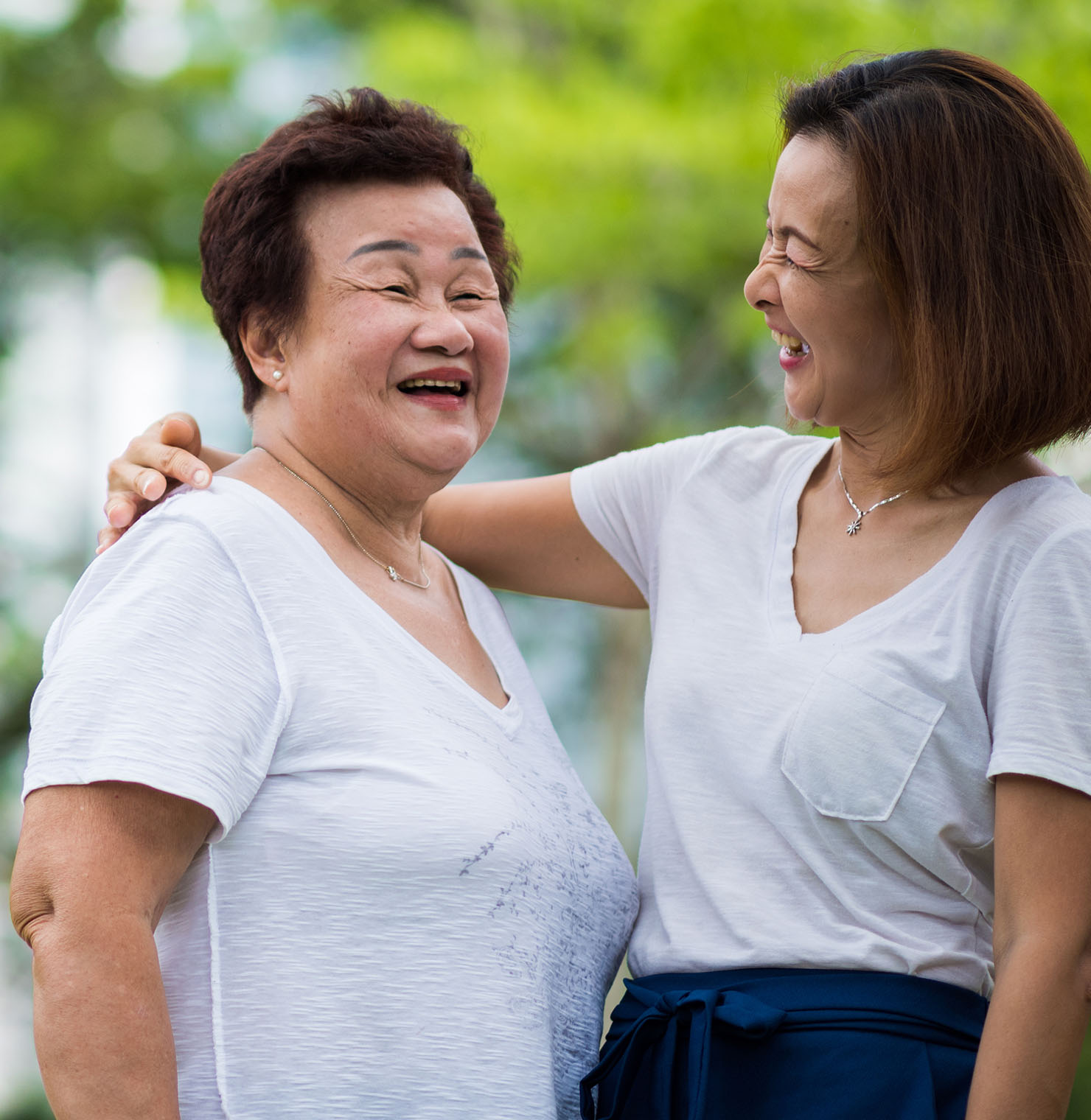 A young woman and her mother, smiling outside