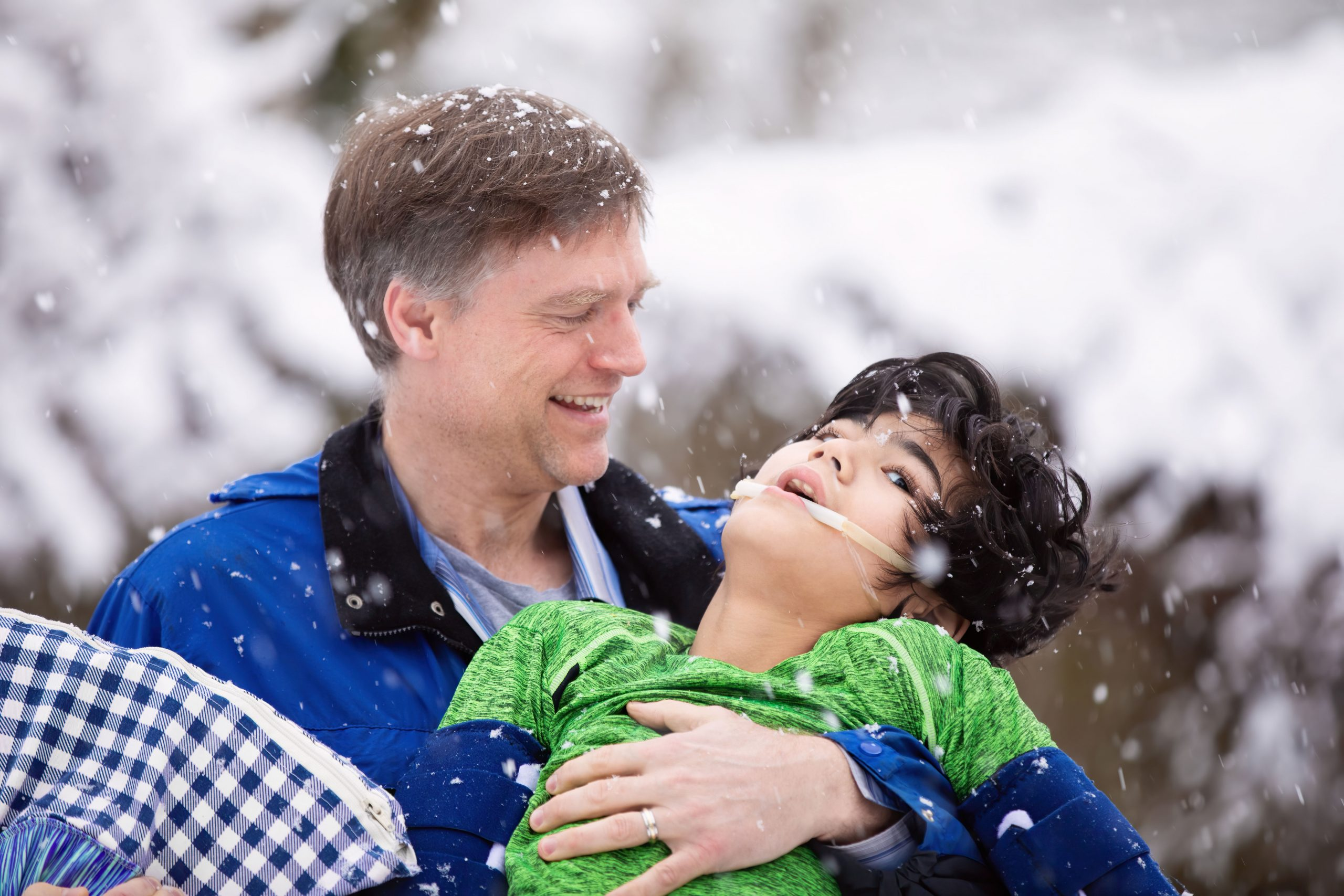 Smiling father holding disabled young son in his arms outdoors during snowfall. Child has cerebral palsy.