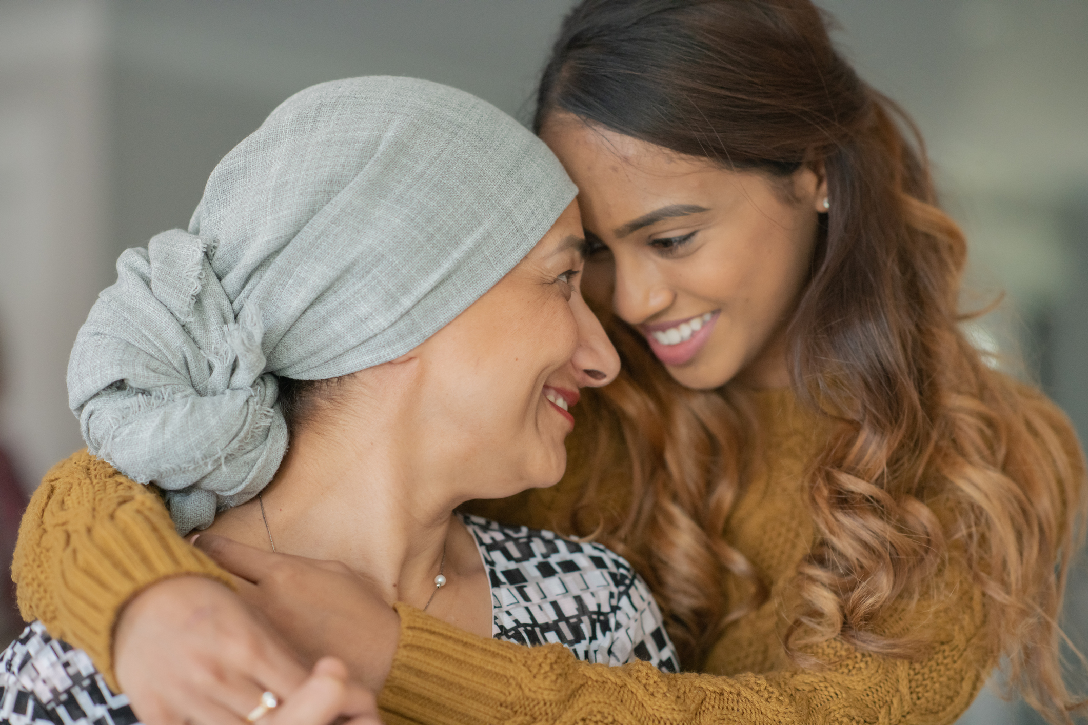 A young woman holds and comforts her mother, a cancer patient