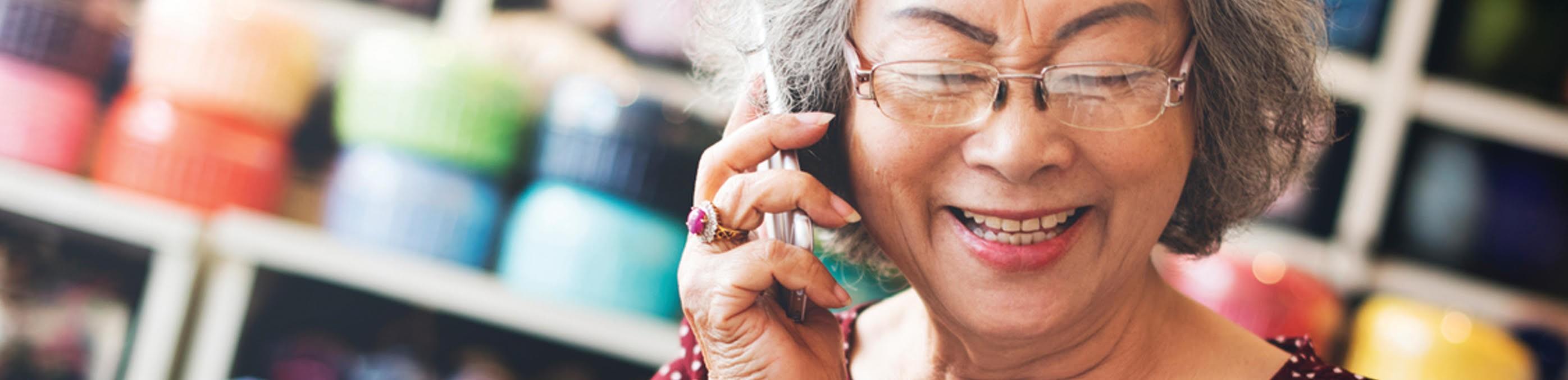 Une dame souriante prend des notes en parlant sur son téléphone cellulaire
