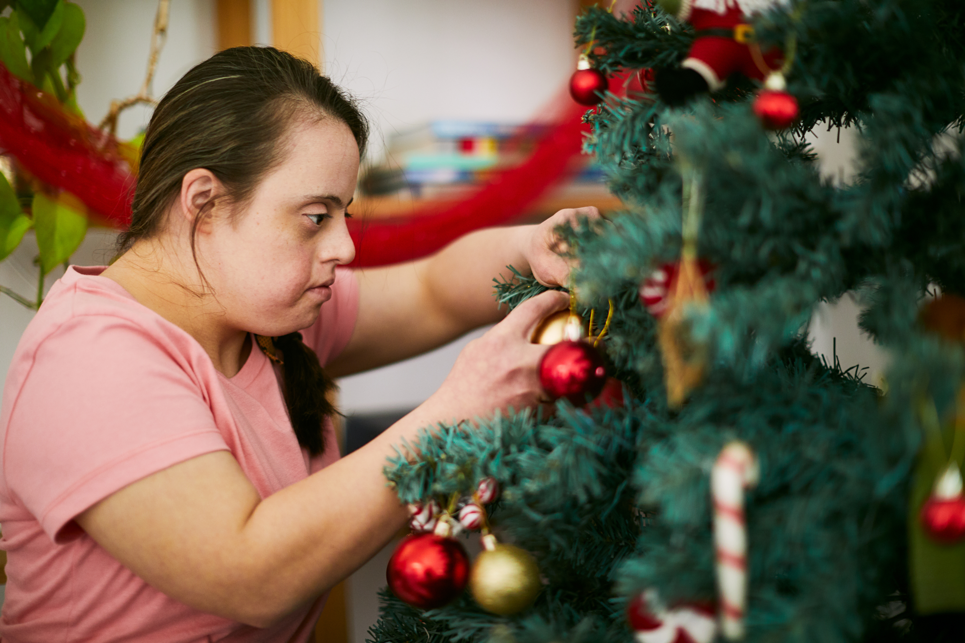 Young woman decorating a Christmas tree. Christmas on Buenos Aires