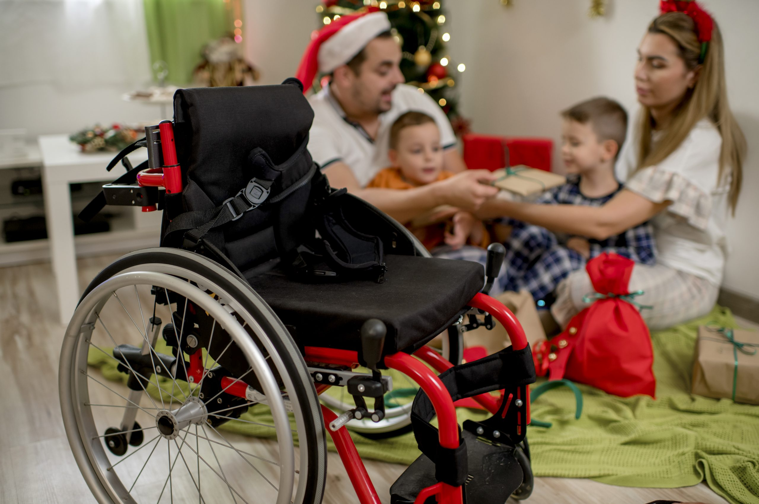 A family around the Christmas tree, a wheelchair in the foreground