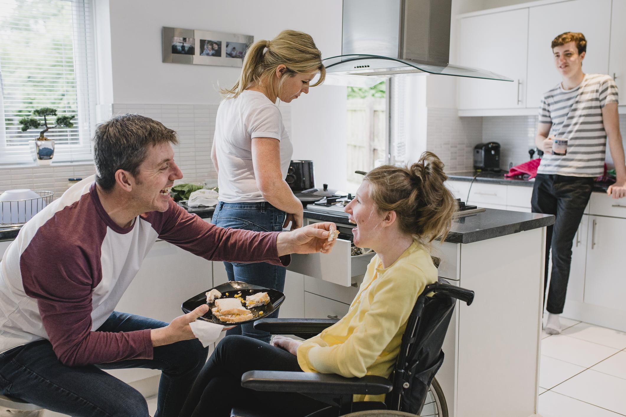 Famille dans la cuisine avec une fille handicapée en fauteuil roulant